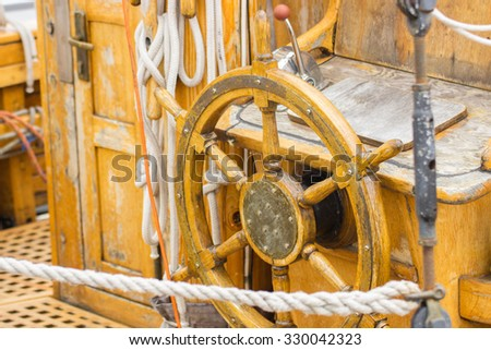 Yachting, helm of old wooden sailboat in port of sailing, rope, steering wheel, details of yacht - stock photo