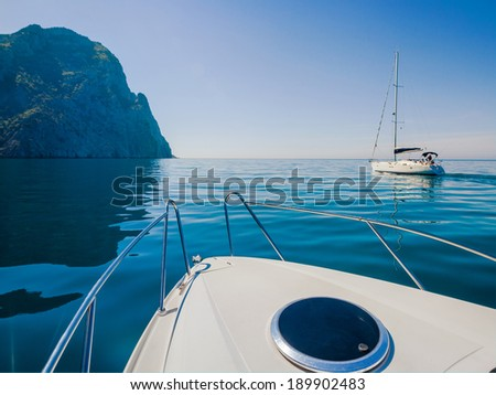 Yachts sailing along the shore in the sea.  - stock photo