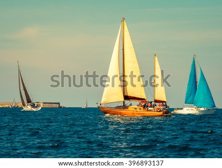 Yachts sailing at waves of the sea. Nautical landscape with sailboat - cruising yacht sailing under full sail taking part in regatta race. Yachting - maritime romantic trip on the yacht. - stock photo
