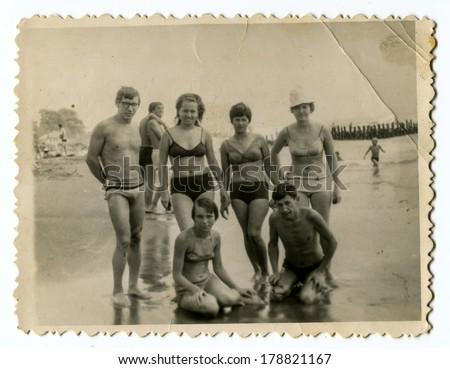 """YALTA, USSR - CIRCA 1960s : An antique photo shows group of people wading in the ocean . """"Soviet people"""" series.  - stock photo"""