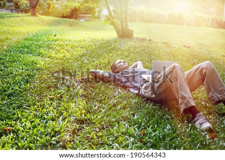 Yang business man is relaxing outdoors with laptop computer - stock photo