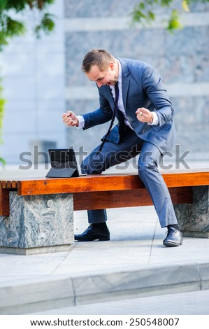 Yang businessman works with tablet computer outdoors. - stock photo