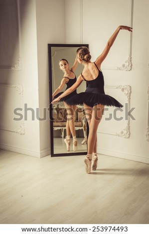 yang lady posing in the studio. Background is white wall. She is in black ballet skirt wearing. She smiles. - stock photo