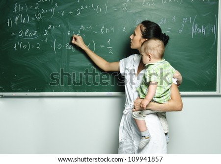 Yang mom with baby boy is writing down formulas in the class board. - stock photo