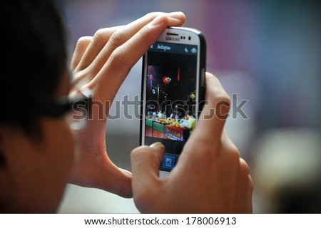 YANGON, BURMA - FEB 10: A temple-goer uses a smartphone to share a photo via Instagram at a Buddhist temple ceremony during festivities ushering in the Chinese New Year on Feb 10, 2013 in Yangon, Burma. - stock photo