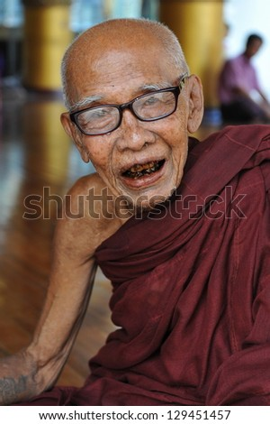 YANGON - FEB 12: A Buddhist monk poses for a photo at Shwedagon Pagoda on Feb 12, 2013 in Yangon, Burma. Built between 6th and 10th century Shwedagon is considered Burma's most sacred Buddhist site. - stock photo