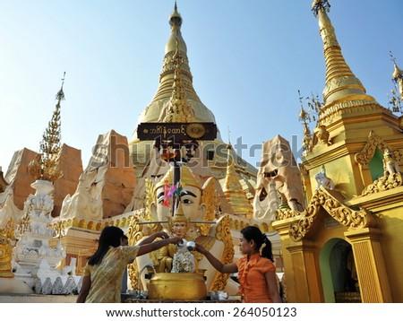 YANGON - FEB 12: Temple goers make merit at Shwedagon Pagoda on Feb 12, 2013 in Yangon, Burma. Built between 6th and 10th century the landmark Shwedagon is Burma's most sacred Buddhist temple. - stock photo