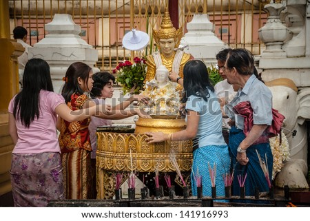 YANGON, MYANMAR - AUGUST 11: people pouring water over the head of Buddha, in Yangon, 11 august 2007. Each person pour water as many times as their age to make their prayers realized - stock photo