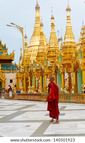 YANGON, MYANMAR (BURMA) - JUNE 25: A Buddhist monk walks in the Shwedagon Pagoda on June 25, 2011 in Yangon, Myanmar, Burma.  There have been recent reports of monks attacking Muslims in Myanmar. - stock photo
