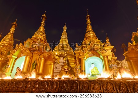 YANGON, MYANMAR-FEB 22: Candle light up in Shwedagon Pagoda on February 22, 2014 in Yangon. It is one of the most famous pagoda in the world and the main attraction of Yangon. - stock photo