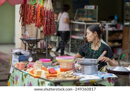 YANGON, MYANMAR - FEBRUARY 10: Burmese female street food vendor in Chinatown on February 10, 2014 in Yangon. Myanmar is ethnically diverse with 51 million inhabitants belonging to 135 ethnic groups. - stock photo