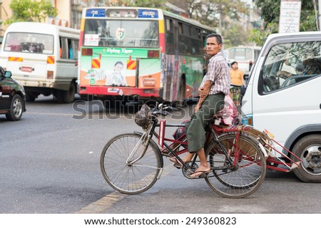 YANGON, MYANMAR - FEBRUARY 10: Burmese street scene with rickshaw in Chinatown on February 10, 2014 in Yangon. Myanmar is ethnically diverse with 51 million inhabitants belonging to 135 ethnic groups. - stock photo