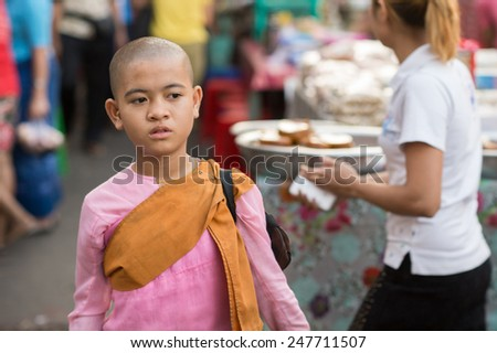YANGON, MYANMAR - FEBRUARY 5: Portrait of a young Burmese Buddhist nun on February 5, 2014 in Yangon. Burmese Buddhist nuns are called Bhikkhuni and they wear pink robes. - stock photo