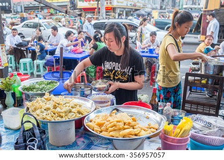 YANGON, MYANMAR â?? FEBRUARY 5: Street scene on Maha Bandoola Road in Chinatown on February 5, 2014 in Yangon. Myanmar is ethnically diverse with 51 million inhabitants belonging to 135 ethnic groups. - stock photo