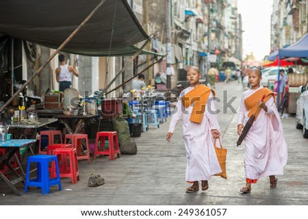 YANGON, MYANMAR - FEBRUARY 5: Two Burmese Buddhist nuns walk in Chinatown on February 5, 2014 in Yangon. Burmese Buddhist nuns are called Bhikkhuni and they wear pink robes. - stock photo