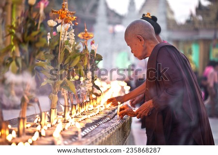YANGON, MYANMAR - JANUARY 29 :A buddhist nun pours oil in for oil lamp at Shwedagon temple Jan 29, 2010, Myanmar to celebrate the full moon festival.  - stock photo