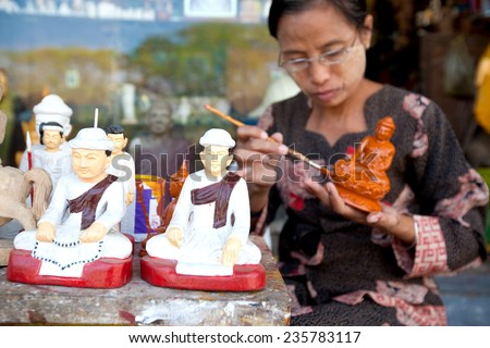 YANGON, MYANMAR - JANUARY 29 : Lady painting  statue of Buddha for souvenirs for tourist,  Jan 29, 2010, Myanmar. Small craft shops line the outter border of the Shwedagon temple in central Yangon. - stock photo