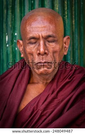 YANGON, MYANMAR - JANUARY 3, 2014: Portrait of ascetic Buddhist monk meditating in Shwedagon Paya pagoda - stock photo
