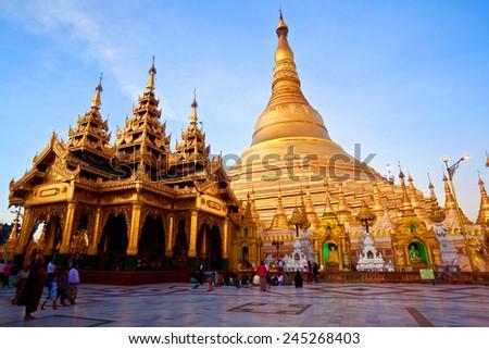 YANGON, MYANMAR - JANUARY 03: Unidentified pilgrims walking around golden Shwedagon Paya during Shwesettaw Festival on January 3, 2011 in Yangon, Myanmar - stock photo