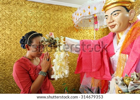 YANGON, MYANMAR - OCT 7: Unidentified people offering for god at Bo Ta Tuang Paya Temple in Botahtaung Pagoda on October 7, 2012 in Yangon traditionally refers to the name of a guardian spirit - stock photo