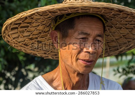 YANGSHUO, CHINA - MAY 01, 2015: An unidentified old farmer in Yangshuo, China.  Agriculture is a vital industry in China, employing over 300 million farmers. - stock photo