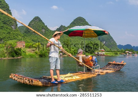 YANGSHUO, CHINA - MAY 01, 2015: Bamboo rafting in the Yulong River surrounded by dramatic landscape of limestone karst. The rafts are built in the traditional design which is still used by fisherman.  - stock photo