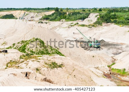 Yantarny, Russia - June 30, 2010: Extracting of amber ore in open-cast mining - stock photo