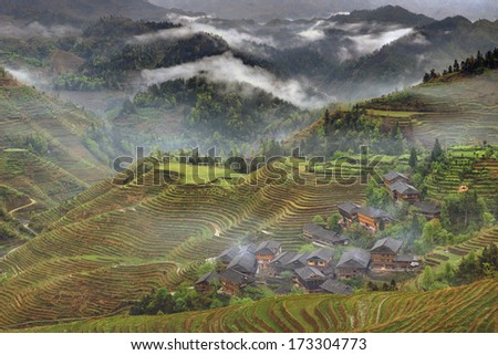 Yao Village Dazhai,  Guangxi, China - April 5, 2010: Rice terraces in highlands of southwestern China, farmhouses, ethnic village. Rice terraces rice paddies Asia, peasant village in mountains China. - stock photo