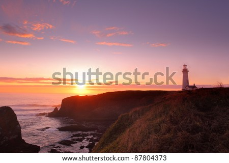 Yaquina Head Lighthouse and Pacific Ocean at sunset - stock photo