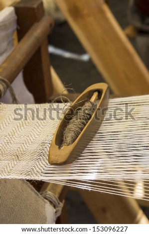 Yarn and shuttle laying on fabric being woven - stock photo