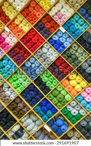 Yarns or balls and of wool are forming lovely colorful pattern. Accessories for haberdashery in a Fabric store shelves. Multi colored picture. - stock photo