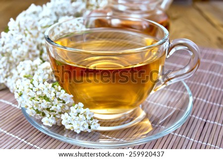 Yarrow tea in a glass cup and teapot, fresh yarrow flowers on a background of bamboo boards and salfeki - stock photo