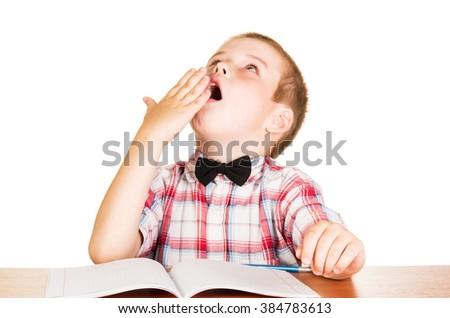 Yawning boy sitting at notebook isolated on white background. - stock photo