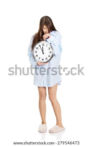 Yawning morning woman in big shirt holding clock. - stock photo