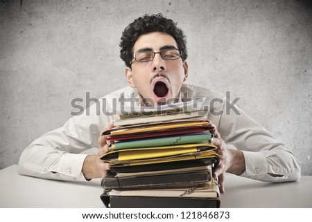 Yawning office worker with a lot of work - stock photo