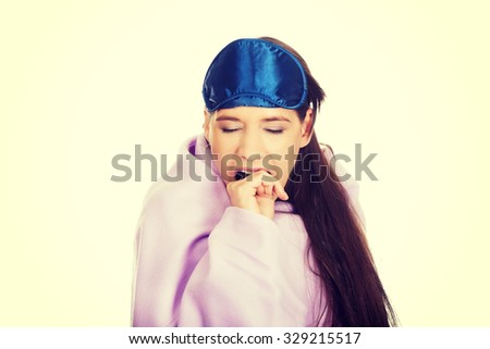 Yawning woman wrapped in coverlet wearing eyes band. - stock photo