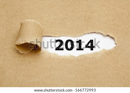 Year 2014 appearing behind torn brown paper. - stock photo