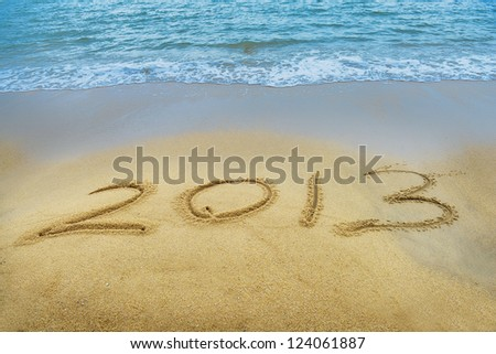 Year 2013 hand written on the white sand in front of the sea - stock photo