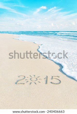 Year number on sea beach sand with the sun rays against wave edge and sky - vacation season 2015 concept - stock photo