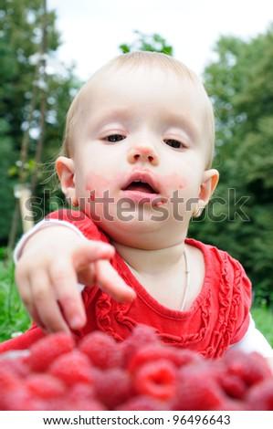 Year-old girl eating raspberries - stock photo