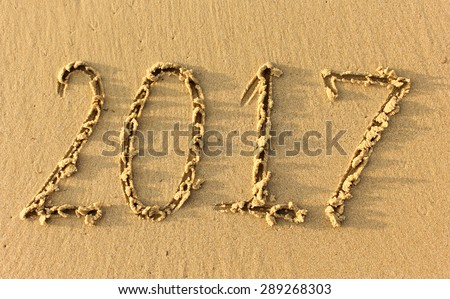 Year 2017 written in the Sand on a Beach against sunset - stock photo