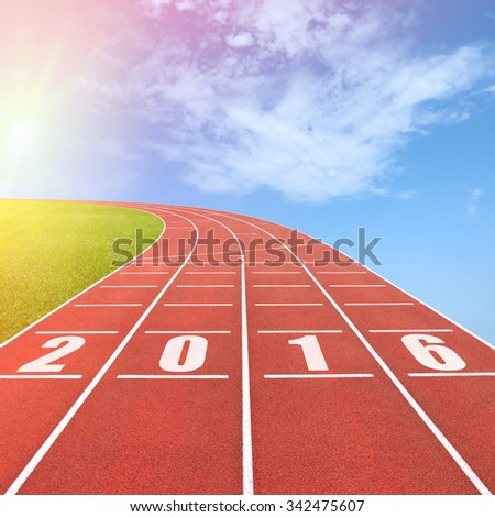 Year 2016 written on running track against sun in sky background - stock photo