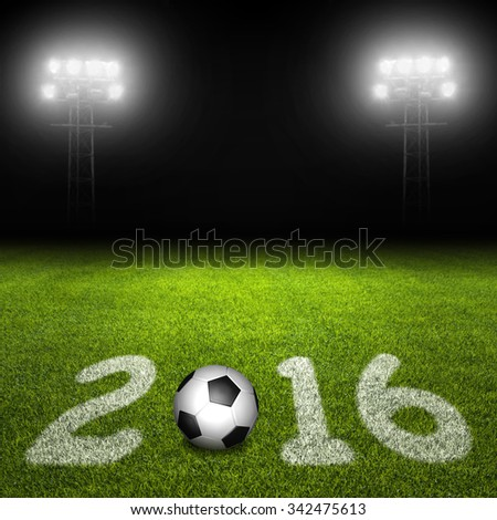 Year 2016 written on soccer field with ball against illuminated stadium lights on black background - stock photo