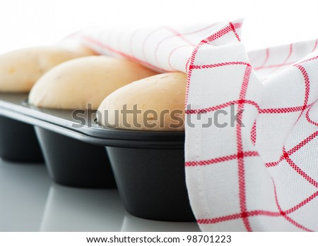 Yeast dough in a muffin pan with a white and red towel on white background as a studio shot - stock photo