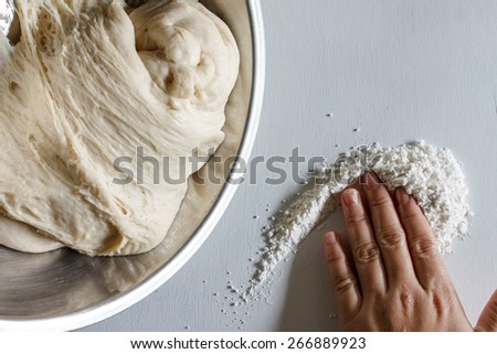 Yeast dough of homemade bread or pizza on wooden board with hand moving catch flour, darkness image - stock photo
