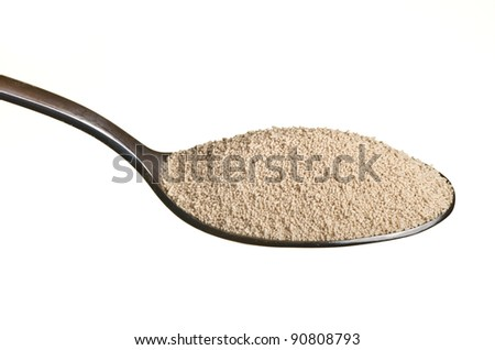 Yeast in a spoon isolated over white background - stock photo