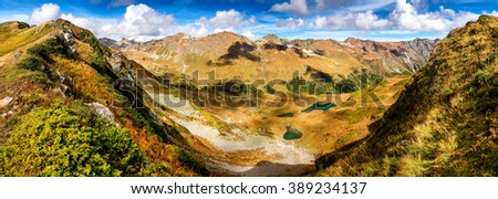 yellow alpine meadows and range of high rocky peaks in the the caucasus mountains valley, Abkhazia, Georgia - stock photo