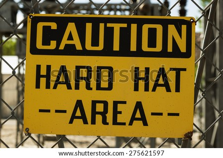 yellow and black caution hard hat area sign wired to a chain link fence - stock photo