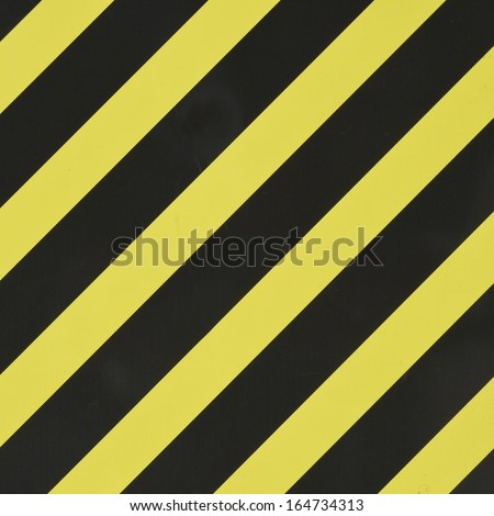 Yellow and black diagonal stripes as an abstract pattern background - stock photo