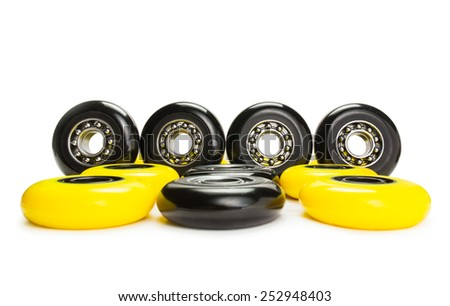 Yellow and black inline skate wheels standing and laying on white background. Isolated - stock photo